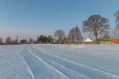 Sneeuwweg in de winterdorp bij dageraad Stock Afbeelding