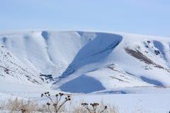 Sneeuwwitte heuvel op de achtergrond van duidelijke hemel Geometrische witte vorm Blauwe schaduw van de heuvel royalty-vrije stock foto's