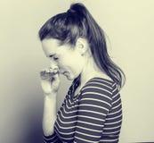 Sneeze αλλεργίας η νέα μύτη γρατσουνιών γυναικών στα λωρίδες μόδας ντύνει hipster την περιστασιακή τοποθέτηση στο ελαφρύ υπόβαθρο Στοκ εικόνες με δικαίωμα ελεύθερης χρήσης
