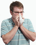 Sneeze. Young man with a cold blowing nose on tissue royalty free stock photo