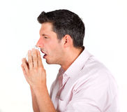 Sneeze. Cold having masculine macho sneezing with red nose into paper tissue royalty free stock photography