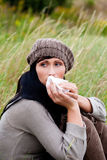 Sneeze woman. Outdoor sitting relaxing female woman cleaning nose Stock Images