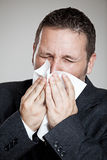 Sneeze. Young business man using a tissue Royalty Free Stock Photos
