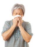 Sneezing asian elderly woman Stock Images