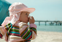 Sneezing babe on beach Royalty Free Stock Photography