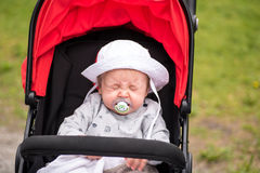 Sneezing baby with sun hat and pacifier sitting in his stroller Royalty Free Stock Photos
