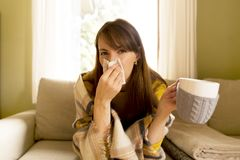 Sneezing and blowing her nose, a young woman struggles with a he. Ad cold and virus Royalty Free Stock Photography