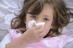 Sneezing child in bed. Suffering from allergy or flu Stock Images