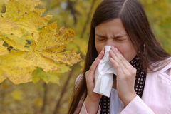Sneezing Girl. Teenage girl sneeze into handkerchief with maple leaf in foreground royalty free stock image