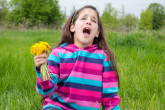 Sneezing girl on meadow with dandelions Royalty Free Stock Photography