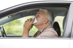 Sneezing man in the car Stock Photography