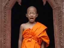Sneezing Novice. UBON RATCHATHANI, THAILAND : Unidentified novice sneezing at window on March 28,2011 in Wat Thung Sri Muang temple Ubon Ratchathani, Thailand royalty free stock photos