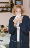 Sneezing senior woman Stock Photos