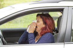Sneezing woman in the car Royalty Free Stock Photo