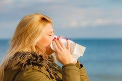 Sneezing woman into handkerchief, outside sunny shot Royalty Free Stock Photos