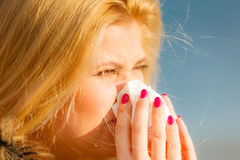 Sneezing woman into handkerchief, outside sunny shot Royalty Free Stock Photography