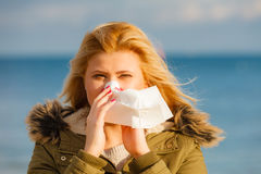 Sneezing woman into handkerchief, outside sunny shot Royalty Free Stock Image