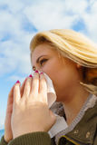 Sneezing woman into handkerchief, outside sunny shot Stock Image