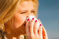 Sneezing woman into handkerchief, outside sunny shot Stock Images
