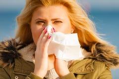 Sneezing woman into handkerchief, outside sunny shot Royalty Free Stock Image