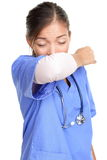Sneezing woman medical nurse doing elbow sneeze. Sneezing woman medical nurse or doctor doing elbow sneeze being sick having the cold flu. Sneezing instruction Royalty Free Stock Photography