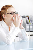 Sneezing woman in the office. Royalty Free Stock Photos