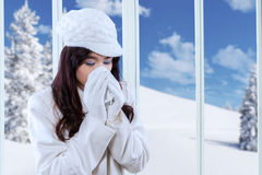 Sneezing woman with a tissue. Pretty girl wearing jacket and using a tissue for sneezing at home in winter day Stock Photography