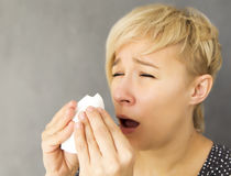 Sneezing woman. Young woman sneezing into handkerchief Royalty Free Stock Photo