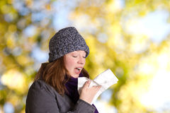 Sneezing young woman outdoors tree Royalty Free Stock Image
