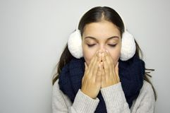 Sneezing young woman sick. Young woman being cold wearing earmuffs, scraf and sweater. Copy space. Stock Photo