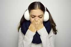 Sneezing young woman sick. Young woman being cold wearing earmuffs, scraf and sweater Royalty Free Stock Images