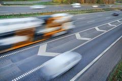 Snel bewegende voertuigen bij motieonduidelijk beeld stock foto