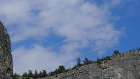 Snel bewegende witte wolken boven de klippen stock videobeelden