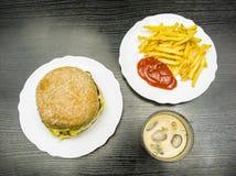 Snel geplaatst voedsel - rundvleeshamburger, frieten met ketchup en kola stock afbeelding
