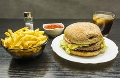 Snel geplaatst voedsel - rundvleeshamburger op een plaat, een kom van frieten a stock afbeeldingen