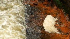 Snel schuimend water tussen zandsteenrotsen, oranje sedimenten op vuile bank Diep die rivierbed in zandsteenblok wordt gehouwen stock video