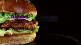 Snel voedsel, close-up Hamburger met gebakken karbonades, greens, tomaat en uien die, langzaam op een houten Raad op een zwarte s stock footage