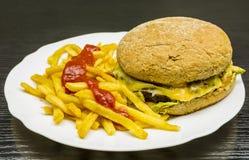 Snel voedsel Een plaat met een rundvleeshamburger, frieten en ketchup royalty-vrije stock fotografie