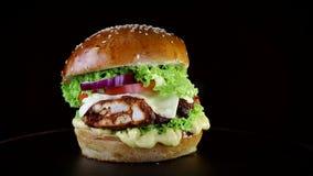 Snel voedsel Hamburger met gebakken karbonades, greens, tomaat en uien die, langzaam op een houten Raad op een zwarte achtergrond stock footage