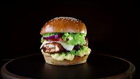 Snel voedsel Hamburger met gebakken karbonades, greens, tomaat en uien die, langzaam op een houten Raad op een zwarte achtergrond stock video