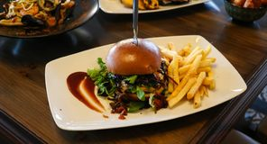 Snel voedselconcept Hamburger met frieten op witte plaat Sluit omhoog mening, onduidelijk beeldachtergrond stock fotografie