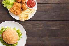Snel voedselreeks gebraden kip, frieten en hamburger op houten Stock Afbeeldingen