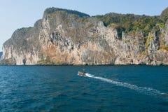 Snelheidsboot het drijven op blauw water voorbij rotsachtige heuvels van Thailand Royalty-vrije Stock Foto's