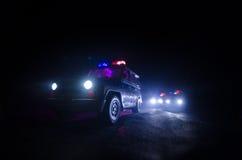 snelheidsverlichting van politiewagen in de nacht op de weg Politiewagens op weg die zich met mist bewegen Selectieve nadruk jach royalty-vrije stock afbeelding