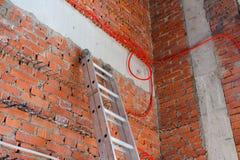 Snelle ladder bij de bakstenen muur en de draden stock foto