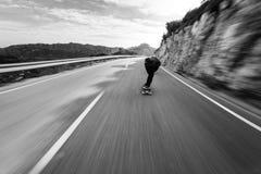 Snelle longboard van het snelheidsonduidelijke beeld bergaf royalty-vrije stock afbeelding