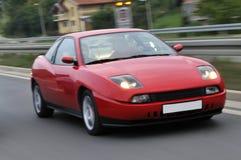 Snelle sportwagen die onderaan de weg rent royalty-vrije stock fotografie