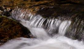 Snelle stroomstromen onder stenen Stock Afbeeldingen