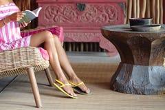 Snello paga di bella donna che si siede su un sof? rosa e che legge un libro Interno nello stile etnico Fine in su fotografia stock