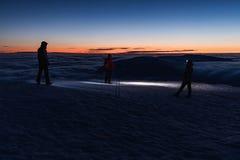 Snezka山的峰顶在Krkonose山的冬天 小组有光的游人在Snezka山顶  图库摄影